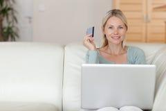在线长沙发预订节假日的妇女 免版税库存图片