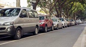在线,停放的汽车行的汽车在城市街道路旁的  库存图片