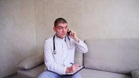 在细胞沟通并且与患者谈判负责任的男性医生的画象,坐长沙发在办公室  影视素材