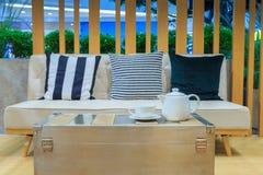 在织品沙发的三个枕头和在桌上的茶具做从 免版税库存图片