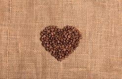 在织品织地不很细棕色背景的咖啡粒心脏 免版税库存照片