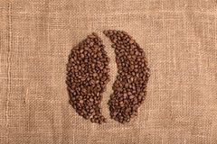 在织品织地不很细棕色背景的咖啡粒 免版税库存图片