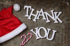 在织地不很细木背景的红色圣诞老人帽子和感谢您木 图库摄影