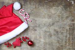 在织地不很细木背景的红色圣诞老人帽子 免版税库存图片