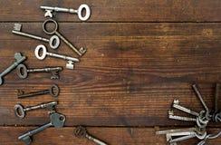 在织地不很细木背景的老钥匙 库存图片