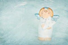 在织地不很细背景的逗人喜爱的蓝色色的天使 图库摄影