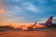 在终端的泰国微笑航空公司停车处在乌隆他尼国际机场(UTH)的日落期间在东北区域的泰国 库存照片