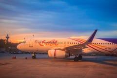 在终端的泰国微笑航空公司停车处在乌隆他尼国际机场(UTH)的日落期间在东北区域的泰国 免版税库存图片