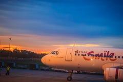 在终端的泰国微笑航空公司停车处在乌隆他尼国际机场(UTH)的日落期间在东北区域的泰国 库存图片