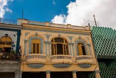 在经典样式的传统建筑与在蓝天背景的五颜六色的门面与云彩的 哈瓦那 古巴 免版税库存图片