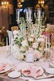 在经典样式的装饰的典雅的宴会桌 用白花花束从玫瑰和毛茛的装饰 库存图片