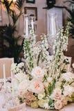 在经典样式的装饰的典雅的宴会桌 用白花花束从玫瑰和毛茛的装饰 图库摄影