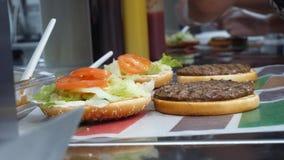 在经典汉堡包的准备的特写镜头 ?? 厨师加沙拉和蕃茄到在汉堡小圆面包的油煎的炸肉排 股票录像