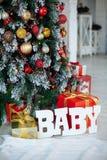 在经典红色纸和木信件婴孩包裹的圣诞礼物,与圣诞树的背景 复制空间 免版税库存照片