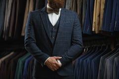 在经典背心的商人反对衣服行在商店 免版税图库摄影