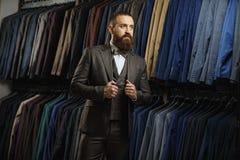 在经典背心的商人反对衣服行在商店 图库摄影