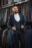 在经典背心的商人反对衣服行在商店 免版税库存图片