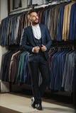 在经典背心的商人反对衣服行在商店 免版税库存照片