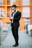 在经典衣服的英俊的有胡子的商人使用一个巧妙的电话,当站立在办公室的阳台时 库存图片