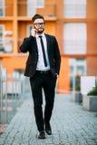 在经典衣服的英俊的有胡子的商人使用一个巧妙的电话,当站立在办公室的阳台时 免版税库存图片