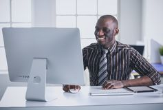 在经典衣服的英俊的美国黑人的商人使用一台膝上型计算机并且微笑着,当工作在办公室时 库存图片