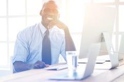 在经典衣服的英俊的美国黑人的商人使用一台膝上型计算机并且微笑着,当工作在办公室时 免版税库存照片