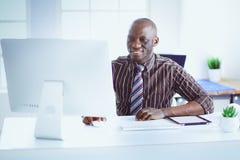在经典衣服的英俊的美国黑人的商人使用一台膝上型计算机并且微笑着,当工作在办公室时 免版税库存图片