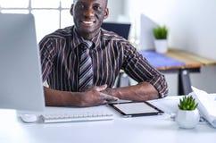 在经典衣服的英俊的美国黑人的商人使用一台膝上型计算机并且微笑着,当工作在办公室时 库存照片