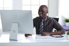 在经典衣服的英俊的美国黑人的商人使用一台膝上型计算机并且微笑着,当工作在办公室时 图库摄影