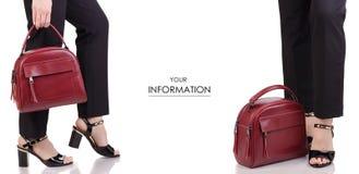 在经典黑色裤子黑亮漆鞋子的女性腿有红色皮包在手中时尚秀丽辅助部件集合样式的 免版税库存图片
