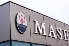 在经销权大厦前面的玛莎拉蒂意大利豪华车厂公司商标 免版税库存照片