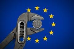 在绑制钳的硬币在欧洲旗子背景  免版税库存图片