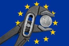 在绑制钳的硬币在欧洲旗子背景  库存照片