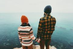 在结合在一起使手的爱男人和妇女的夫妇在峭壁旅行愉快的情感生活方式概念的海上 年轻家庭trave 库存照片
