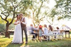 在结婚宴会的新娘和新郎使叮当响的玻璃外面在后院 免版税图库摄影