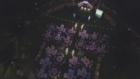 在结婚宴会装饰的寄生虫飞行或者婚姻周年,在室外的庭院里,承办的设置椅子和 股票视频