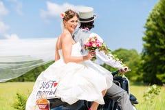 在结婚的小型摩托车的婚礼夫妇 免版税库存照片