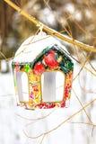 在结构树树干的积雪的五颜六色的birdfeeder  免版税库存图片