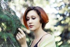在结构树附近的一个俏丽的女孩 免版税库存照片