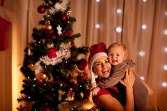 在结构树附近的婴孩美丽的圣诞节母&# 库存照片