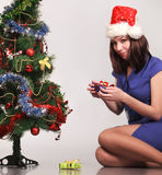在结构树附近的美丽的圣诞节礼品女&# 图库摄影