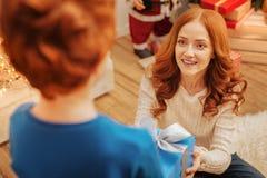 在给儿童圣诞节礼物的微笑的妈妈的顶视图 库存照片