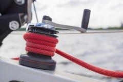 在绞盘的红色绳索在船身 免版税库存照片