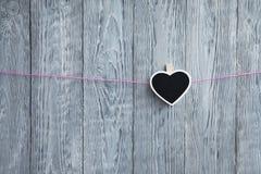 在绳索吊的一一点心脏在木灰色背景的一条桃红色绳索 库存照片
