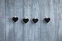 在绳索的一点心脏在木灰色背景的一条桃红色绳索垂悬 免版税图库摄影