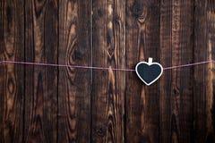 在绳索的一点心脏在木背景的一条桃红色绳索垂悬 免版税库存照片
