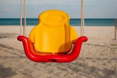 在绳索的儿童` s明亮的摇摆在沙子天空海背景  免版税图库摄影