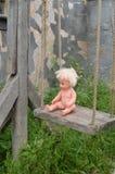 在绳索的古老木摇摆 在摇摆的塑料赤裸玩偶 免版税库存照片