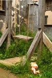 在绳索的古老木跷跷板在没有孩子的大厦附近 免版税图库摄影