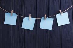 在绳索的四个蓝色空白的贴纸在黑木板条backg 免版税库存图片